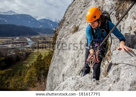 Young woman climbing high above valley - stock photo