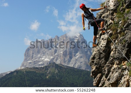 Young woman climbing in the Dolomits, Italy - stock photo