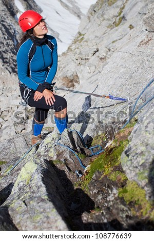 Young woman climbing in the mountains - stock photo