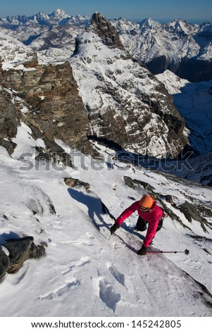 Young woman climbing in winter mountains - stock photo