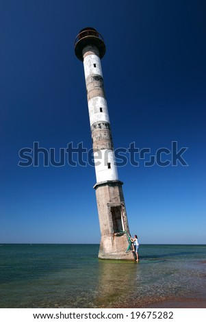 Young woman climbing into abandoned leaning lighthouse.