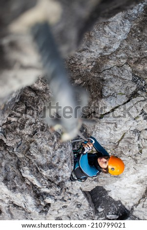 Young woman climbing on a steep rock face - stock photo
