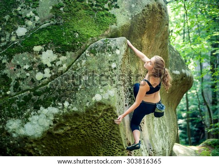Young woman climbing on large boulders outdoor summer day - stock photo