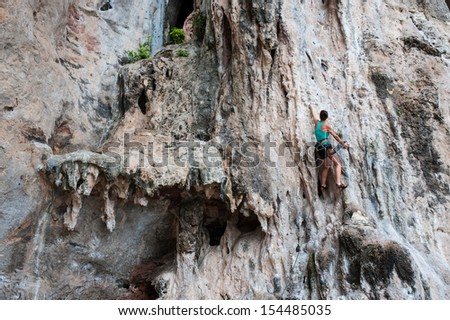 Young woman climbing on limestone rock - stock photo