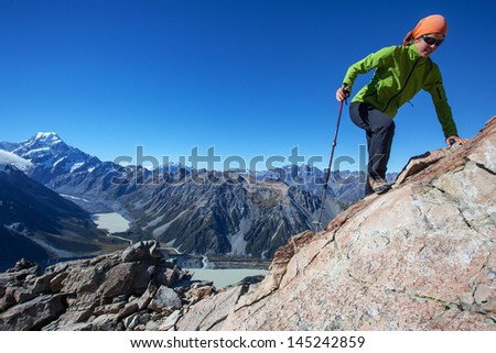 Young woman climbing rocky mountain ridge - stock photo
