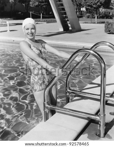 Young woman climbing up the ladder of a swimming pool - stock photo