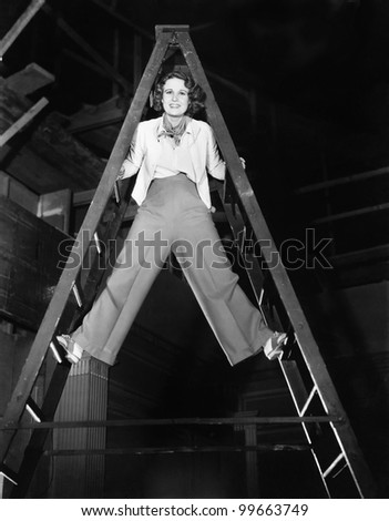 Young woman climbs a ladder to the top - stock photo