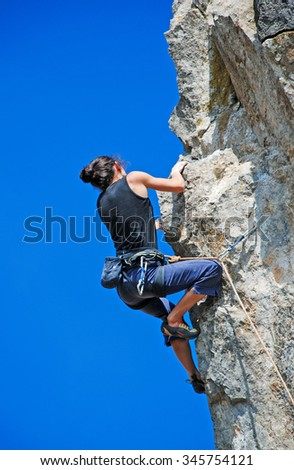 Young woman climbs on a rocky wall - stock photo