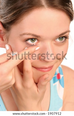 Young woman, close-up, inserting a contact lens in her eye - stock photo