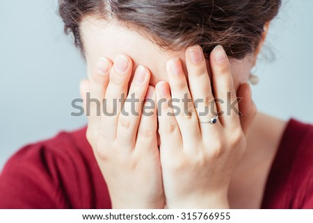 young woman closes eyes with her hands