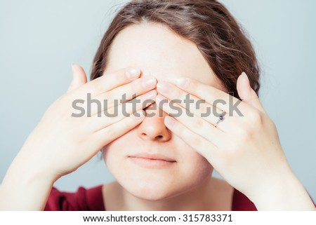 young woman closes eyes with her hands - stock photo