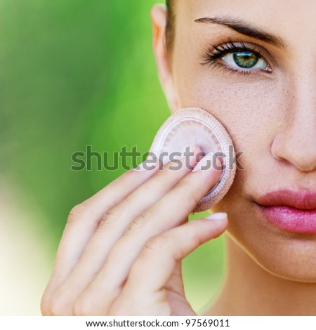 young woman closeup applying foundation - stock photo