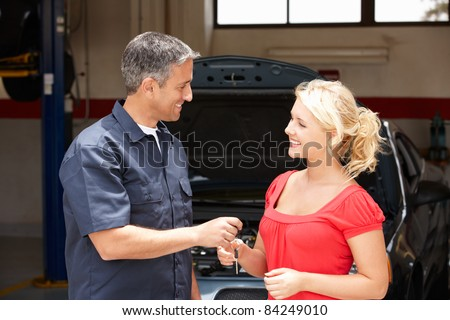 Young woman collecting care from repair shop - stock photo