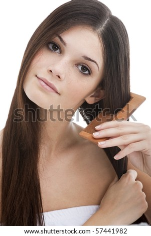 Young woman combing her hair - stock photo
