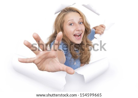 Young woman coming out of a hole tearing on the white paper - stock photo