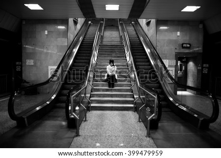 Young woman commuter in subway metro station alone at night,pensive thinking lost woman doesn't know where to go.Sitting on stairs,waiting for someone.Danger,scared woman.Robbed.Toned,noise added - stock photo