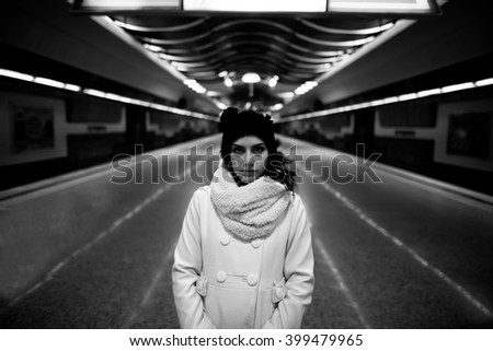 Young woman commuter in subway metro station alone at night,pensive thinking lost woman doesn't know where to go.Running away,leaving town.Danger,scared woman.Robbed,abused woman.Toned,noise added - stock photo