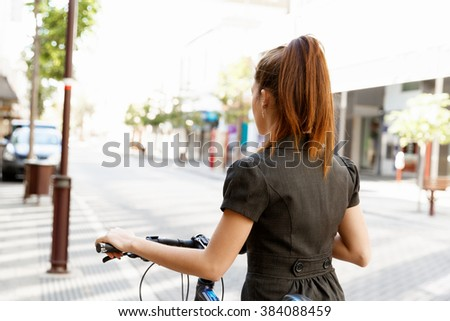 Young woman commuting on bicycle - stock photo