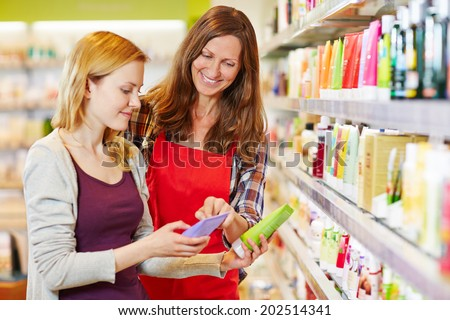 Young woman comparing cosmetics products with saleswoman in a drugstore - stock photo