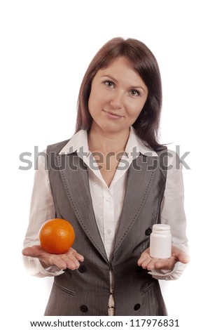 Young woman comparing fruit, orange with medicine over white background