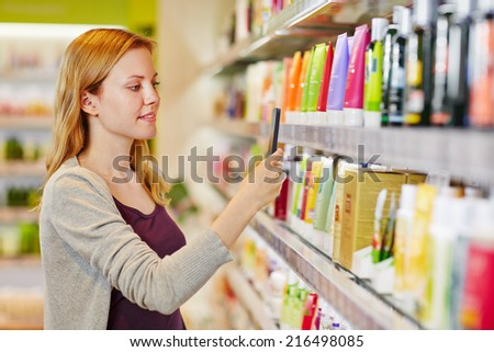 Young woman comparing prices with a smartphone app in a drugstore - stock photo