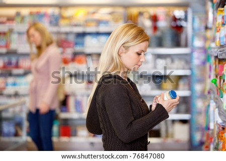 Young woman comparing products in the supermarket with people in the background - stock photo