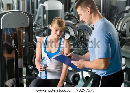 Young woman completing personal fitness plan with trainer healthy club - stock photo