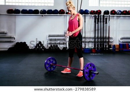 Young woman concentrate before barbells exercise at gym - stock photo