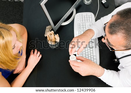 Young woman consulting her doctor, he has a prescription drug bottle in his hand - stock photo