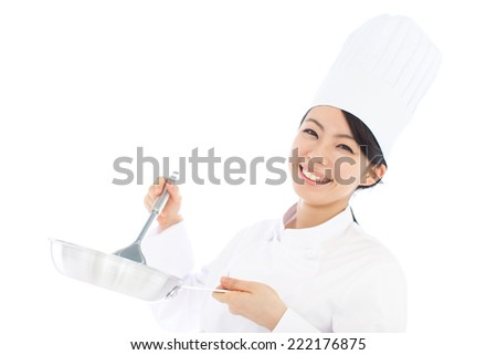 young woman cook holding frying pan and turner isolated on white background