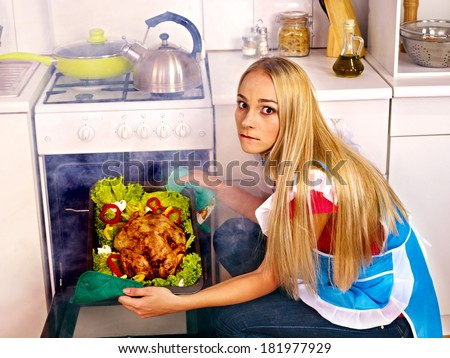 Young woman cooking chicken at kitchen.