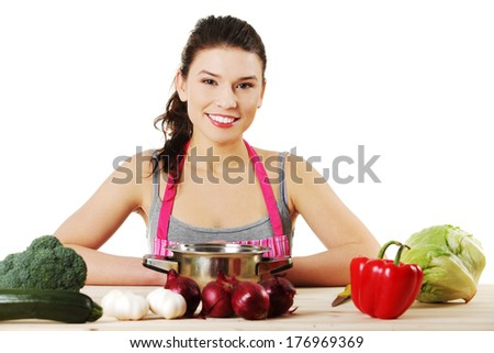 Young woman cooking healthy food in pot, isolated on white