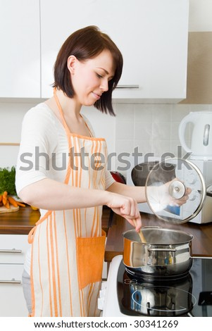 Young woman cooking in her kitchen - stock photo