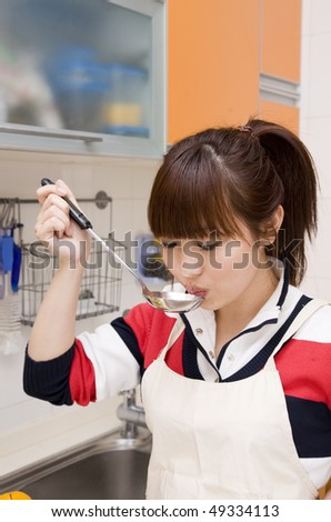 young woman cooking in the kitchen and tasting soup. - stock photo