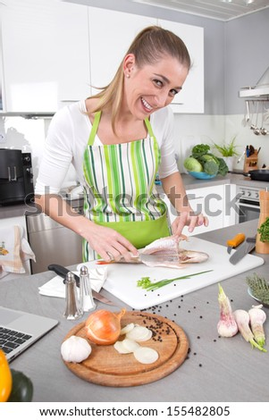 Young woman cooking in the kitchen - fresh fish.