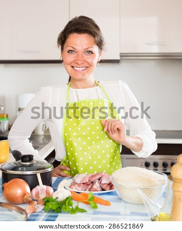 Young woman cooking meat with vegetable at domestic kitchen - stock photo