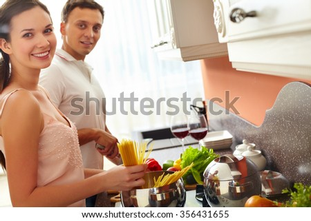 Young woman cooking spaghetti while her husband cutting vegetables - stock photo