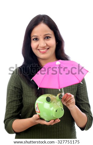 Young woman covering a piggy bank with umbrella-Concept of money savings and protection - stock photo