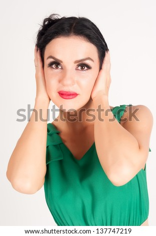 Young woman covering her ears by hands on white background - stock photo