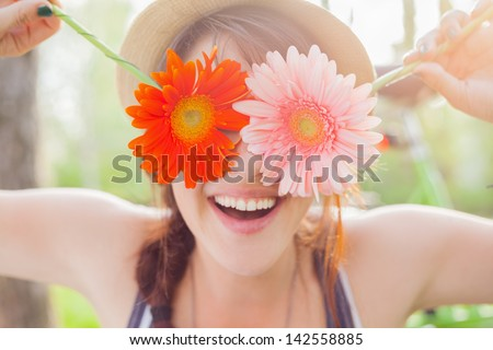 Young woman covering her eyes with fresh colorful flowers. Enjoying spring time - stock photo
