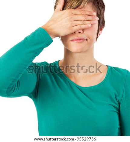 Young woman covering her eyes with her hand. Studio shot against a white background. - stock photo