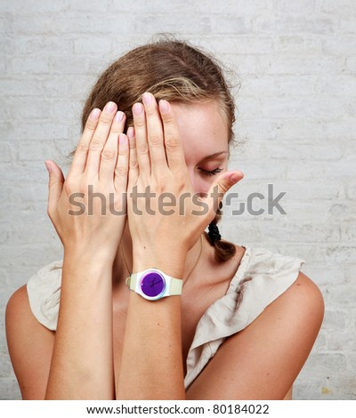 young woman covering her face - stock photo