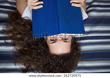 Young woman covering her face with a book lying on the rug. - stock photo