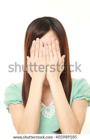 young woman covering her face with hands - stock photo