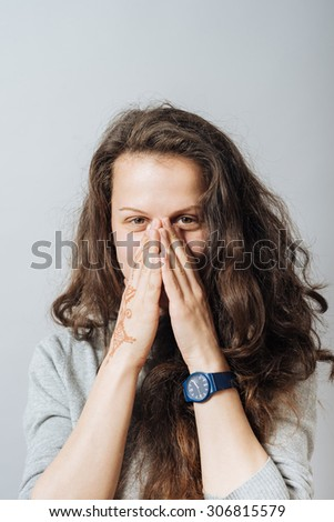 Young woman covering her face with her hands. On a gray background. - stock photo