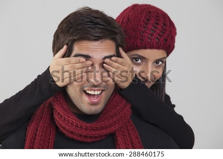 Young woman covering man's eyes - stock photo