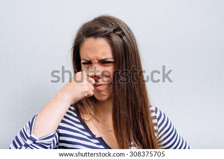 young woman covering nose, something stinks - stock photo