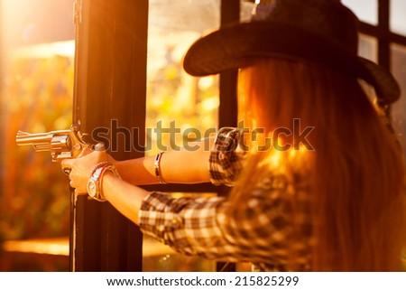Young woman cowboy shooting. Focus on gun. - stock photo