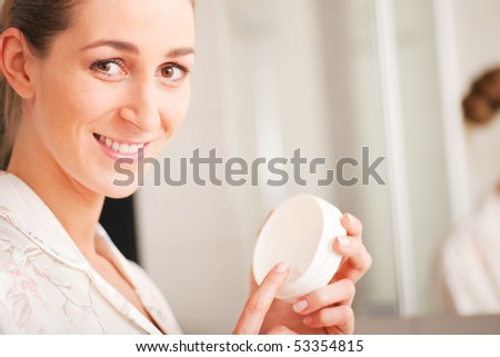 Young woman creams her face to keep the skin smooth and soft