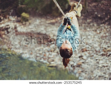 Young woman crossing a river with tyrolean traverse - stock photo